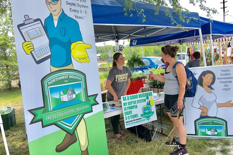 Event guest speaks with staffer at septic system maintenance information booth at local event.