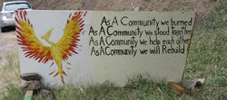 Hand painted road sign with image of a Phoenix says 'As a Community we burned, As a community we stood together, As a community we help each other, As a community we will Rebuild'.