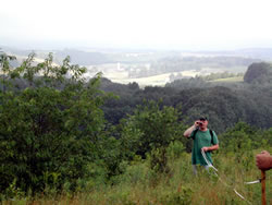 [image:] A field Forester takes measurements with a farm valley in the background