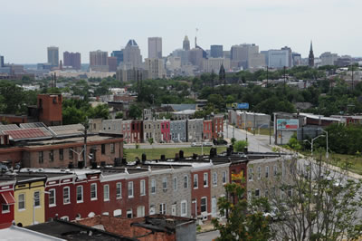 Baltimore neighborhood of row houses with urban tree canopy and downtown skyline in background.  Photo by Morgan Grove, US Forest Service.