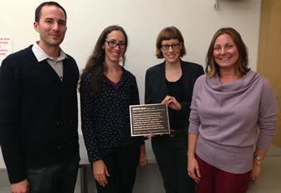 [photo:] from left: Mark Weckel, Catherine Seavitt, Denise Hoffman Brandt, and Sarah Aucoin. Seavitt and Brandt presented Weckel with a bronze plaque commemorating the presence of coyotes in Central Park in 2010. Weckel hung the plaque in his office at the American Museum of Natural History, which faces Central Park