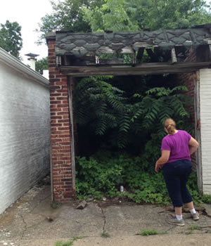 [photo:] Citizen peers into deteriorating, abandoned garage filled with overgrown vegetation.