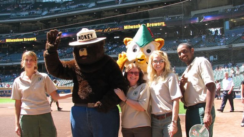 Smokey Bear, Woodsy Owl, and Forest Service employees share important messages at a 2006 Milwaukee Brewers baseball game.