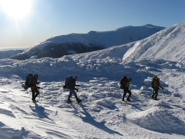 Four climbers cross a stretch of snowy mountain